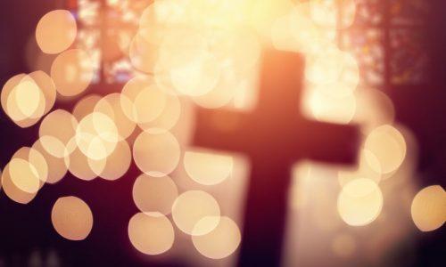 Abstract defocussed cross silhouette in church interior against stained glass window concept for religion and  prayer